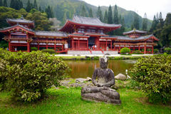 Gray Buddha statue in front of buddhist temple. Gray Buddha statue in front of Byodo-in temple Royalty Free Stock Photos