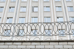 Gray building is fenced with barbed wire. Symbol of  dictatorial and authoritarian regime. Royalty Free Stock Photo