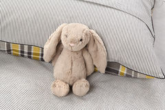 Gray Bunny. A stuffed animal is leaning against a pillow Royalty Free Stock Photography