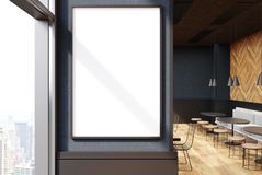 Gray cafe interior, poster close up. Close up of a vertical framed poster on a cafe wall. Large windows, gray and wooden walls and round tables with sofas and Stock Photo