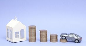 Gray car model and home with coins in the form of a histogram on a purple background. Concept of lending, savings, sale, lease of