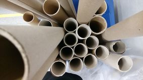 Gray cardboard tubes from fabrics. Concept: material, fabric, manufacture, garment factory, new samples of fabrics. stock photos