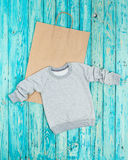Gray casual kids pullover. Front Top view. Other clothing for children and adults in my portfolio. Can place your own print/ Rustic style blue background. Bag Royalty Free Stock Photography