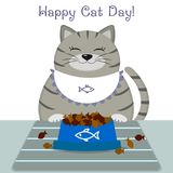 A gray cat in an apron sits at a table, next to a blue plate with a fish-shaped food. A cute gray cat in an apron sits at a table next to a blue plate with a Royalty Free Stock Photos