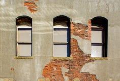 Gray Cement Building avec trois Windows et briques rouges exposées image stock