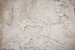 Gray cement wall with traces of the brush on the crumbling plaster. textural composition stock image