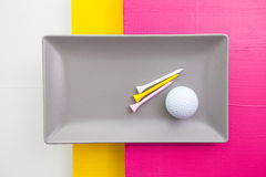 Gray ceramic dish with golf equipments Royalty Free Stock Photo