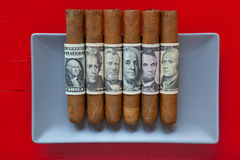 Gray ceramic dish and luxury Cuban cigars with US dollar banknot Stock Photos