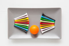 Gray ceramic dishes with golf balls and wooden tees Royalty Free Stock Photography