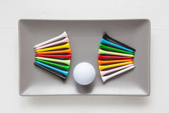 Gray ceramic dishes with golf balls and wooden tees Stock Images