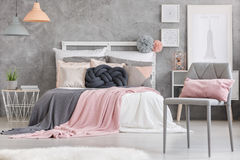 Gray chair with pink pillow. Gray chair with small pink pillow standing in a room with king-size bed stock photography