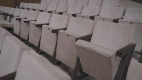 Gray chairs in an empty cinema hall. Empty chairs. The failure of the film at the box office. Concert hall without spectators and fans. The night before the stock video footage