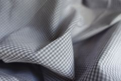 Gray checkered fabric in soft folds Stock Image
