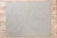 Gray cloth napkin on brown rustic wooden background top view with copy space.  royalty free stock photo