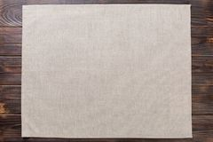 Gray cloth napkin on rustic dark wooden background top view with copy space.  royalty free stock photo
