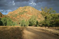 Gray clouds over the country road. Dramatic gray clouds over the country road under the red hill covered with shrubs. South Australia Stock Image
