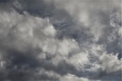 Gray clouds and wisps. Darkening gray clouds billow through a brighter sky in the background stock image