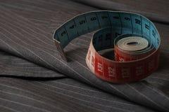 Gray Coat a strisce e un nastro di misura fotografia stock
