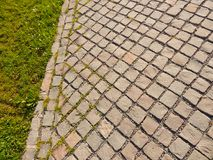 Gray cobblestone road close-up with green grass Royalty Free Stock Photography