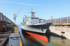 Navy ship repair. Gray color navy ship on dry dock for maintenance and repair stock photography