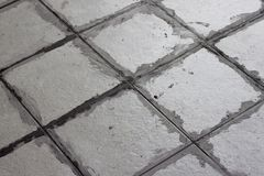 Gray color of new grout tile on tile gray. Gray color of new grout tile on tile gray for the final step for flooring in Thailand Royalty Free Stock Photography