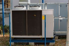 Gray commercial cooling unit for central ventilation system with big ventilation unit standing outdoor on the ground covered by fa. Gray cooling unit for central Royalty Free Stock Photo