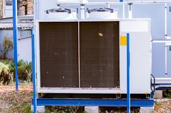 Gray commercial cooling unit for central ventilation system with big ventilation unit standing outdoor on the ground covered by fa. Gray cooling unit for central Stock Photography