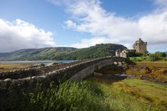 Gray Concrete Bridge Connecting to Gray Concrete Castle With Green Hills Background Under Blue Sky and White Clouds during Daytime Stock Photography