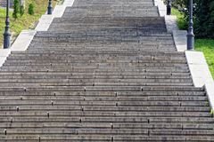 Gray concrete steps on a long stone staircase. On a city street stock image