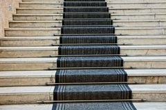 Gray concrete steps of the stairs and black carpet track. Gray concrete steps of the stairs and a black carpet in the hall stock photography