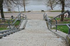 Gray concrete steps of the stairs and iron handrails in the park on the shore of the reservoir. Gray concrete stairs and iron handrails in a park on the shore of stock image