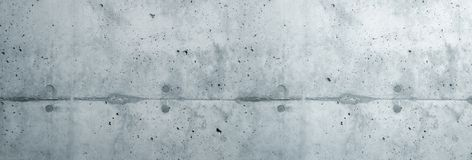 Gray concrete wall coarse facade made of natural cement with holes and imperfections separating layers as an empty background. Gray concrete wall coarse facade royalty free stock images