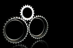 Gray connected gears closeup over black background Stock Images