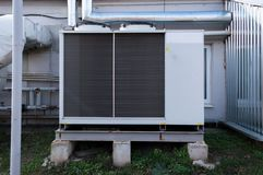 Gray commercial cooling unit for central ventilation system with big ventilation unit standing outdoor on the ground. Gray cooling unit for central ventilation Stock Photography