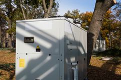 Gray commercial cooling unit for central ventilation standing outdoor on the ground covered by fallen leaves. Gray cooling unit for central ventilation system Royalty Free Stock Photography
