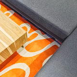Gray corner sofa and orange carpet Royalty Free Stock Photo