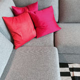 Gray corner sofa with silky red cushions Stock Photography