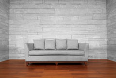 Gray couch chair. On brown wooden floor and white wall Royalty Free Stock Photo