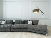 Gray couch and floor lamp against white wall Stock Images