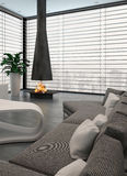 Gray couch in front of modern fireplace Royalty Free Stock Images