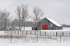 Gray Country Barn With uma porta vermelha em uma paisagem coberto de neve Fotos de Stock