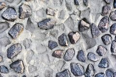 Gray crushed stones on the wall of cement and prints from fallen out royalty free stock photography