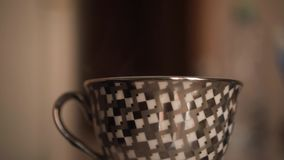 Gray cup on the table. Pour boiling water from the kettle. Side view, view of a couple from a mug. Gray cup with a pattern of rhombuses on the table. Pour stock video footage