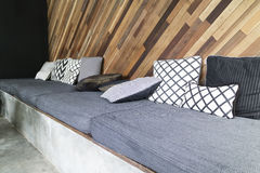 Gray cushion and pillow with slant wooden wall Stock Photos