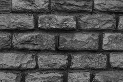 Gray dark gradient background carved from the rock uneven weathered surface hard powerful base design part base of the stone wall royalty free stock photo