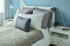 Gray, dark gray and beige pillows on bed with blue wall Royalty Free Stock Image