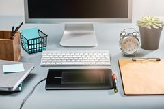The gray desk with laptop, notepad with blank sheet, pot of flower, stylus and tablet for retouching royalty free stock images