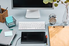 The gray desk with laptop, notepad with blank sheet, pot of flower, stylus and tablet for retouching royalty free stock photo