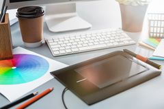 The gray desk with laptop, notepad with blank sheet, pot of flower, stylus and tablet for retouching stock photos