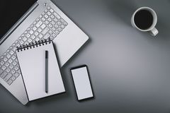 Gray desk with laptop smartphone cup of coffee. top view with co stock image